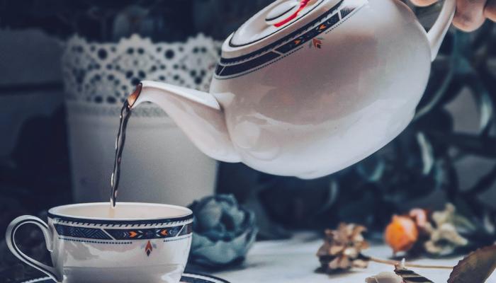 Teapot pouring hot tea into a teacup